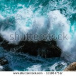 stock-photo-a-beautyful-blue-wave-smashs-against-a-cliff-1018647517